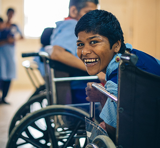 Child in wheelchair smiling